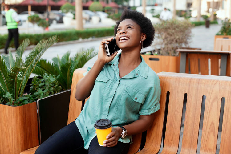 Cheerful young woman talking over smart phone while sitting at cafe