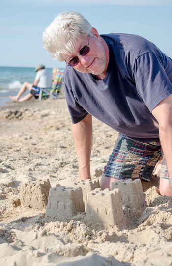 Portrait of man in sunglasses kneeling by castle at beach
