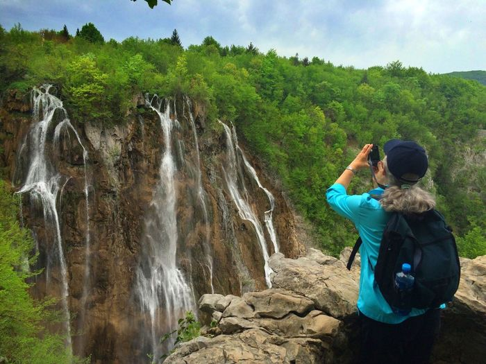 Rear view of woman photographing waterfall at plitvice lakes national park