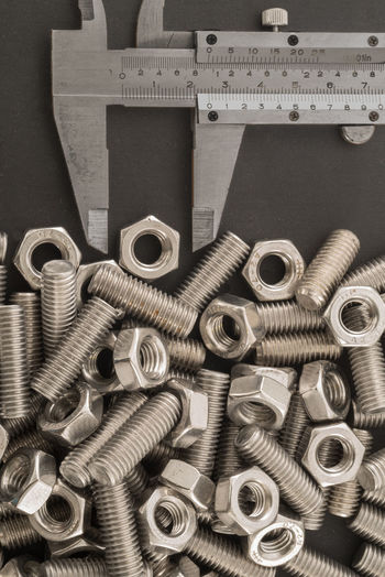 High angle view of nuts and bolts with ruler on table