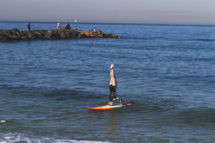 Woman Practicing Headstand On Surfboard In Sea