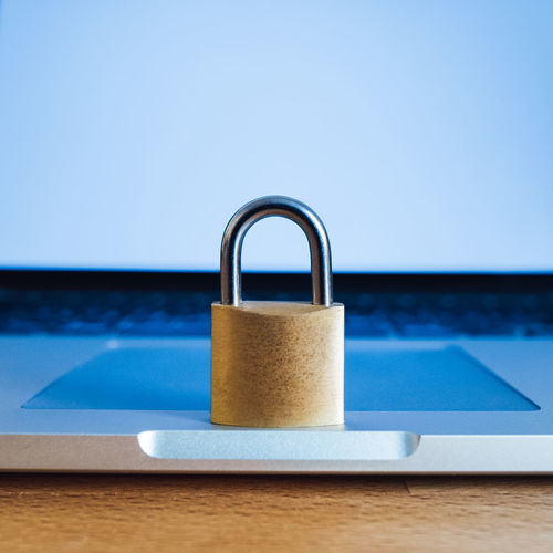 Close-up of padlock on laptop at table