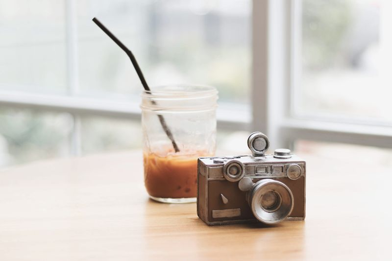 Close-up of old camera and drink in jar on table