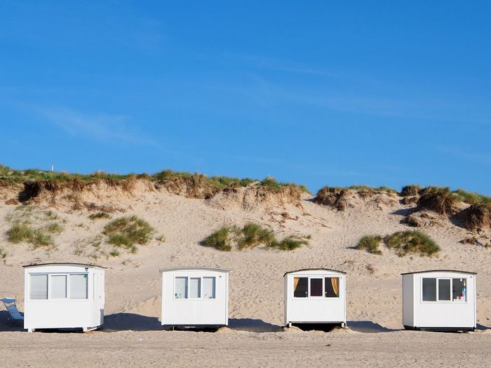 May 2018 Sky Blue Nature Day Land Clear Sky No People Window Sunlight Plant Sand Outdoors Copy Space Scenics - Nature Architecture Land Vehicle Built Structure Side By Side Transportation Beach Cabins Northsea Dunes Dunescape Blue Sky White White Color Marram Grass Beach Shore