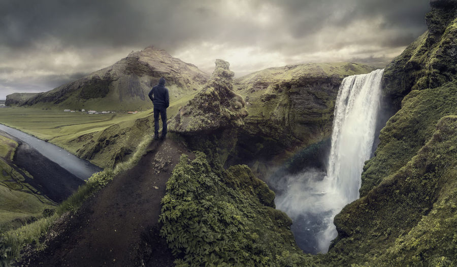 Rear View Of Hiker Standing On Rock By Skogafoss Against Cloudy Sky