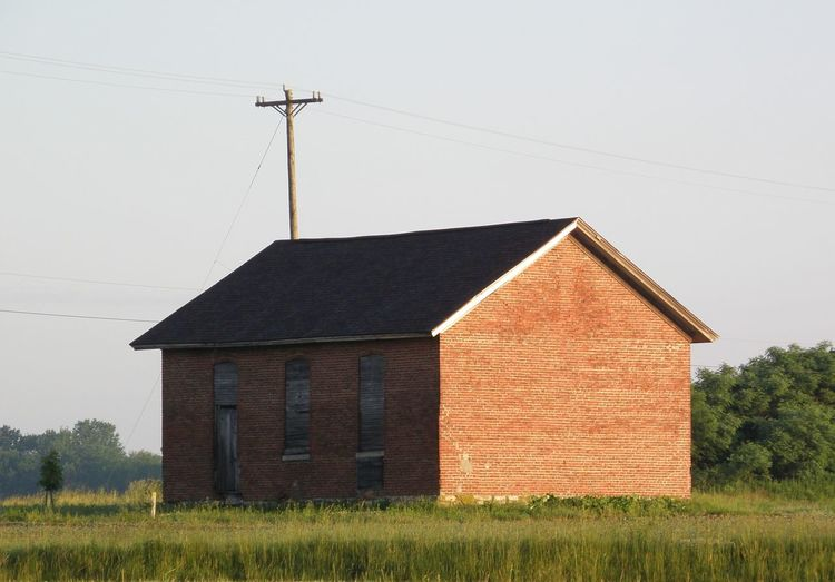 Old Brick Schoolhouse Architecture Brick Built Structure Cable Day Field Grass Grassy Green Color Growth Landscape Nature No People Old Brick Schoolhouse Outdoors Plant Power Line  Rural Scene School House Sky