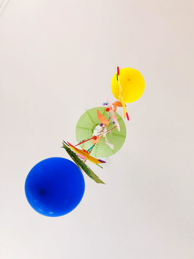 Close-up of multi colored balloons against white background