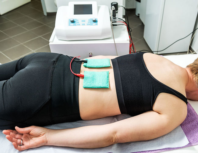 Midsection of woman lying on floor