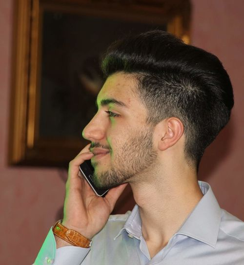 Boy Looking Away While Talking On Mobile Phone