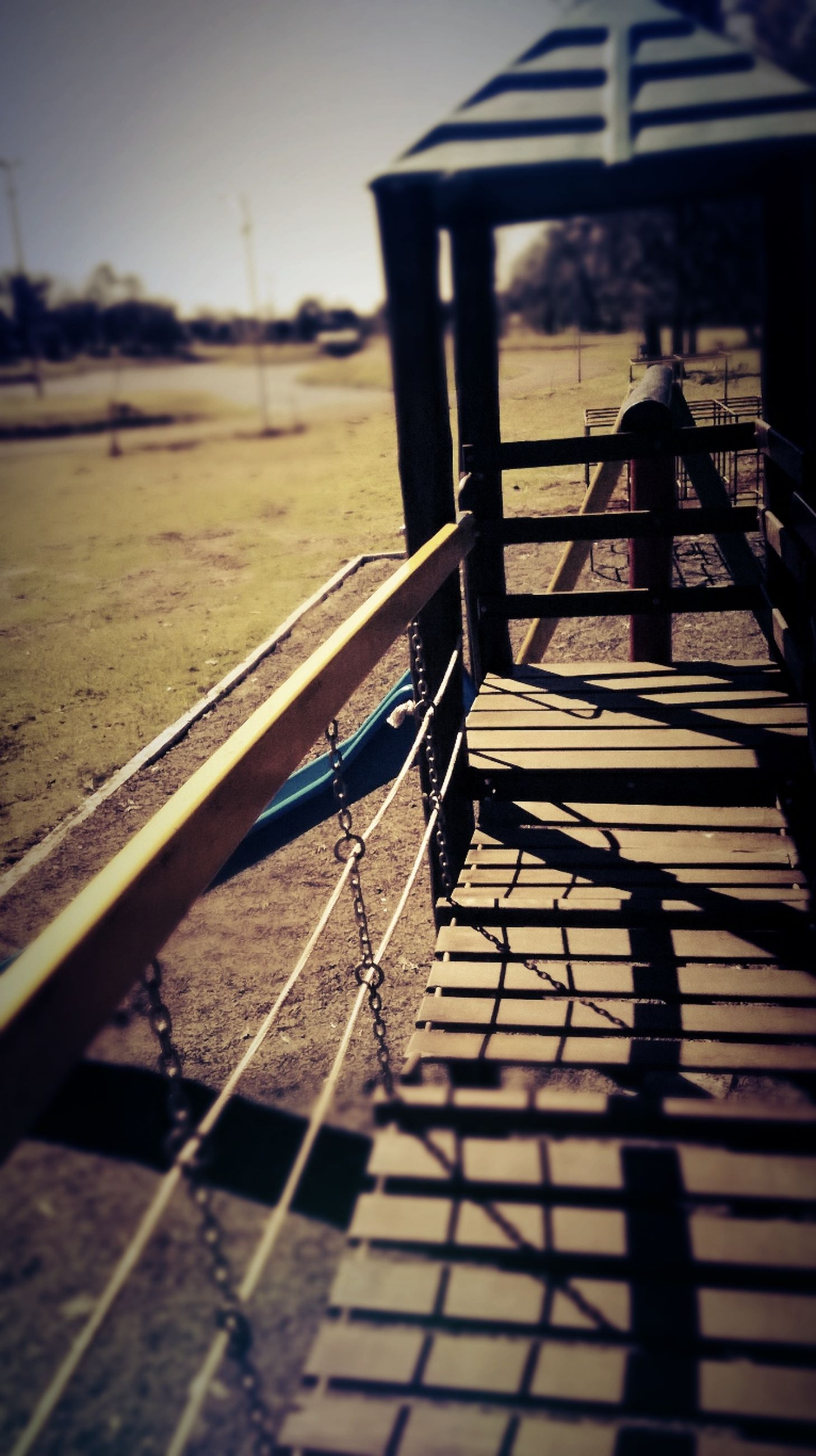 railing, the way forward, empty, sunlight, selective focus, shadow, wood - material, metal, surface level, absence, water, sky, no people, outdoors, transportation, steps, focus on foreground, tranquility, bench, day