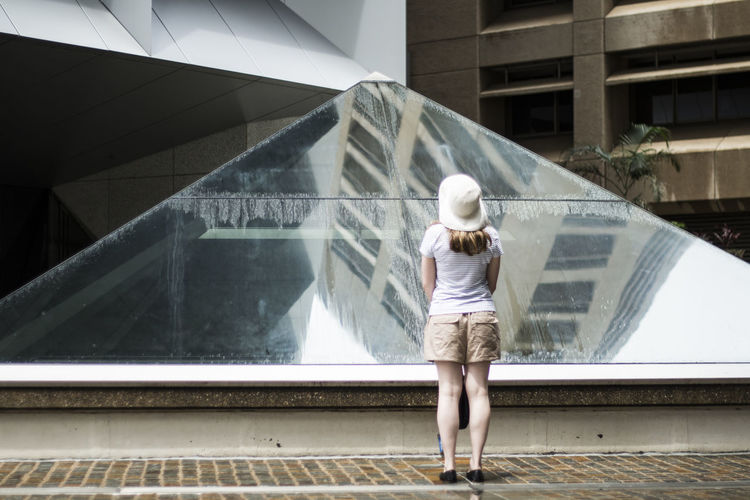 Rear view of woman looking at buildings reflection in glass pyramid