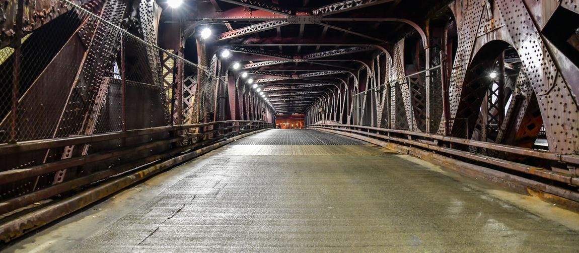 Empty road in illuminated tunnel at night