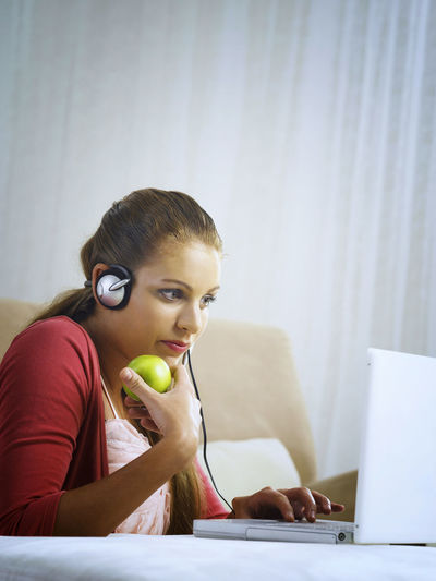 caucasian woman using laptop Apple At Home Online Gaming Blond Hair Casual Clothing Caucasian Charting Communication Connection Ear Phone Headphones Indoors  Laptop Listening Microphone One Person Onlline Real People Sitting Talking Technology Using Laptop Wireless Technology Young Adult Young Women