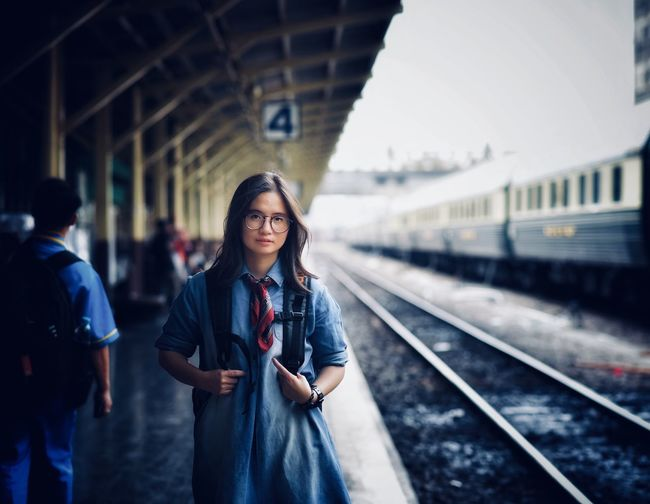 Portrait of smiling young woman standing at railroad station