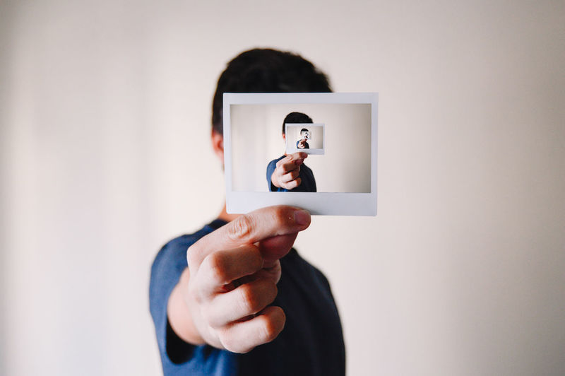 PERSON HOLDING A PHOTOGRAPH OF HIMSELF