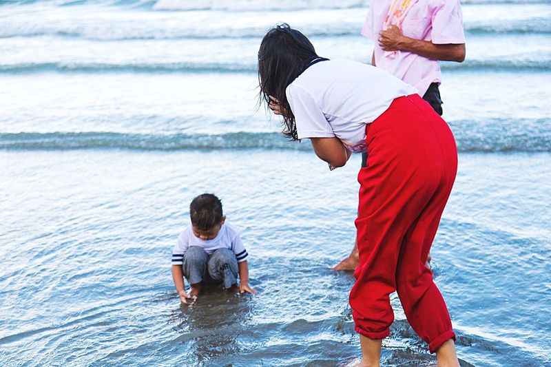 Rear view of father and daughter on sea shore