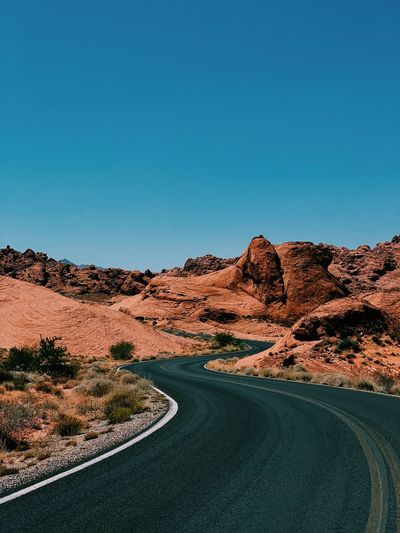 Road amidst red desert against clear blue sky