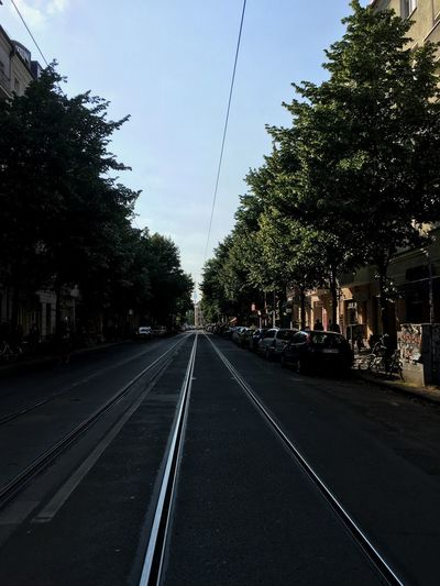View of railroad tracks by road in city