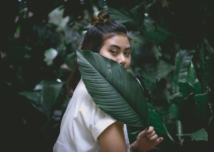 Portrait of young woman covering mouth with leaf against plants