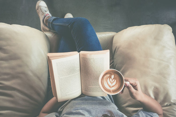 Low section of woman holding coffee cup while reading book on sofa