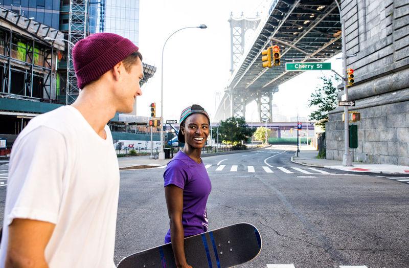 Smiling man and woman holding skateboard walking on road against bridge