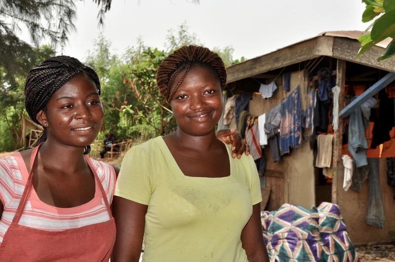 Laundry Hut Social Issue Poverty Developing Country Apron Portrait Smiling Looking At Camera Two People Young Adult Women Happiness Casual Clothing Real People Emotion Adult Front View People Standing Outdoors Sister Twins Family Togetherness Sisters♡ Africa Ghana Faces Of Africa Waist Up