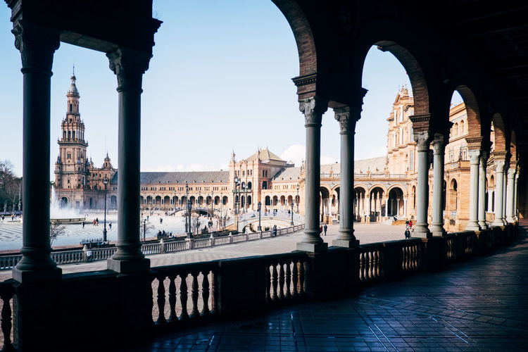 Historic buildings at plaza de espana seen through colonnade against blue sky