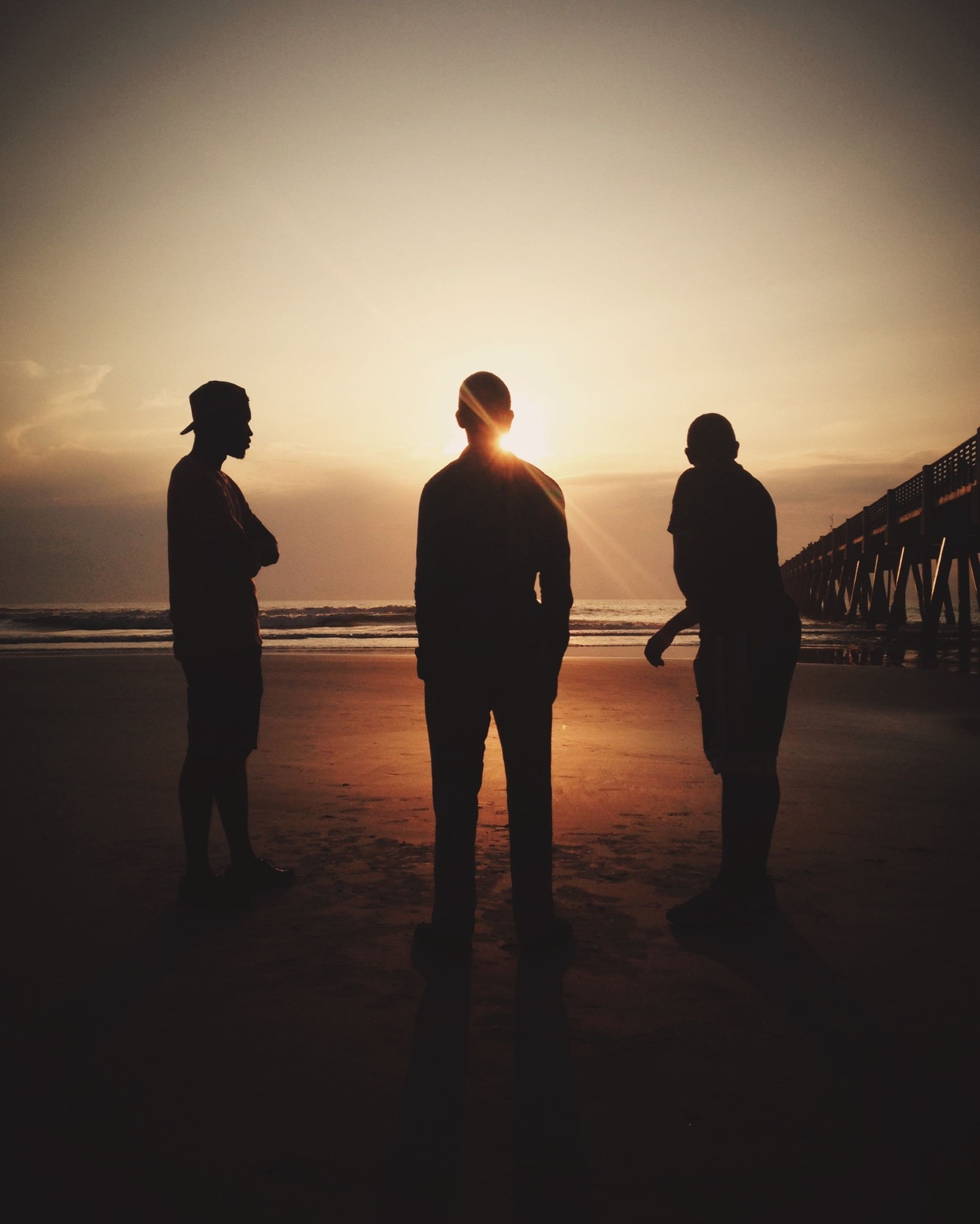 sunset, silhouette, men, full length, togetherness, lifestyles, standing, sky, leisure activity, walking, person, rear view, copy space, clear sky, orange color, sea, beach, bonding