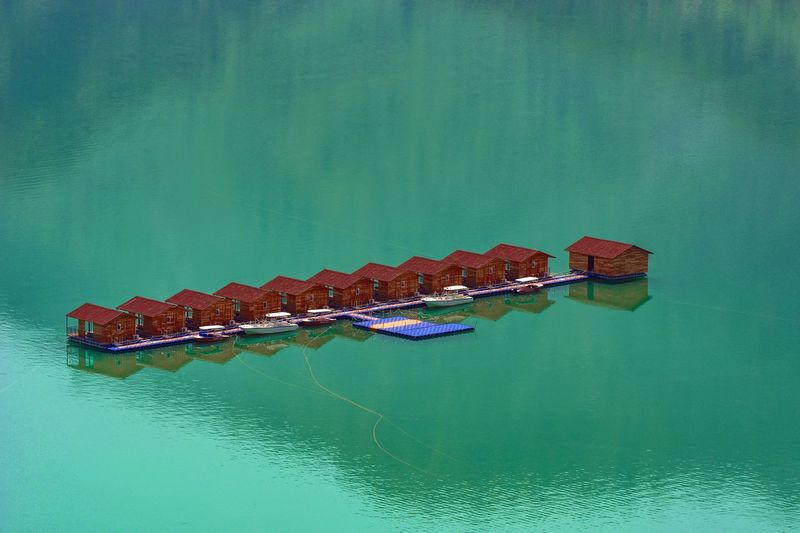 High angle view of boat floating on lake against building