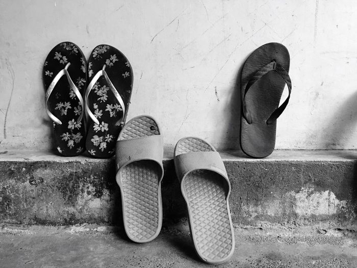 Close-up of footwear against wall