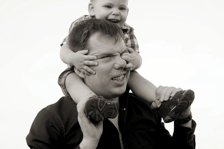Portrait of father and baby boy against clear sky
