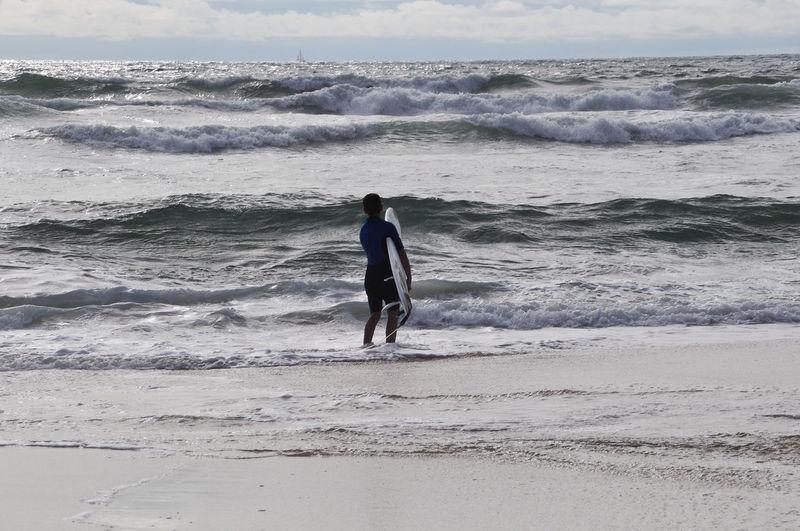 Rear view of man walking on beach against sky