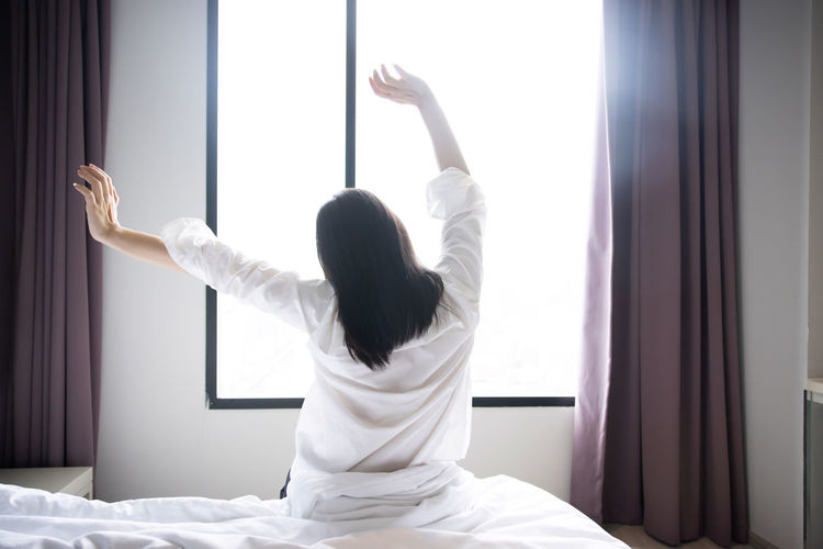 Rear view of woman with arms raised at home