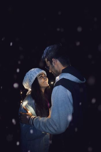 Young couple romancing while standing against sky at night