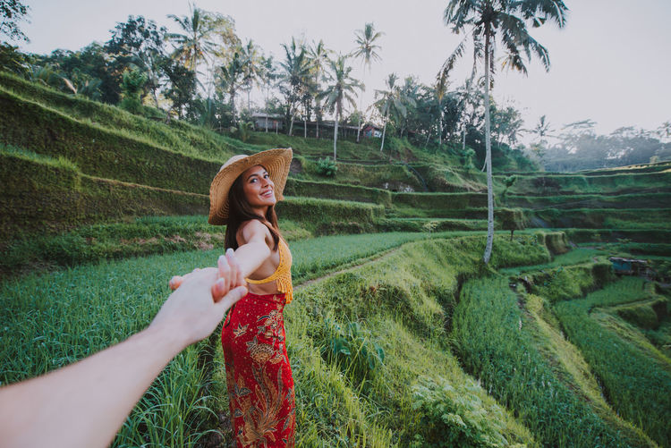 Young woman holding hand at rice terrace