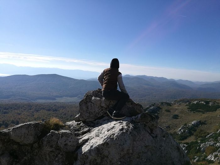 Boy sitting on cliff against mountains