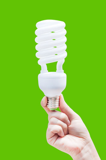 Close-Up Of Person Holding Light Bulb Over Green Background