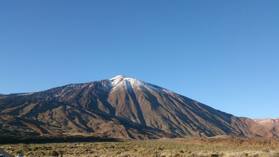 View of volcanic mountain range against blue sky