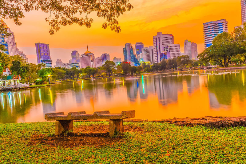 Peaceful lake view park in the capital city with buildings reflection on the water during sunset at Lumpini public park in Bangkok, Thailand. Peace And Quiet Architecture Beauty In Nature Building Exterior Built Structure City Cityscape Day Growth Lake Lumpini Park Nature No People Orange Color Outdoors Peaceful Reflection Scenics Sky Skyscraper Sunset Travel Destinations Tree Urban Skyline Water