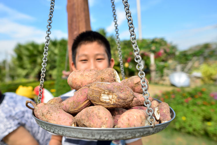 Close-up of sweet potatoes on weight scale against boy