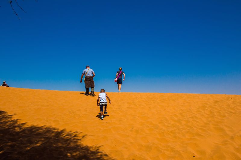Low angle view of family on sand dune in desert against clear blue sky