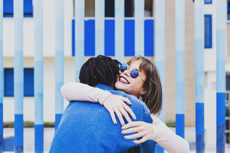 Caucasian young girl wearing sunglasses hugging her afro boyfriend