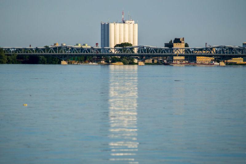 View of bridge against industrial buildings