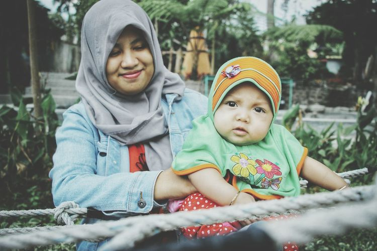 Smiling woman holding daughter amidst ropes in park