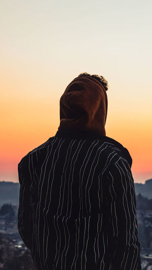 Rear view of man standing against sky during sunset