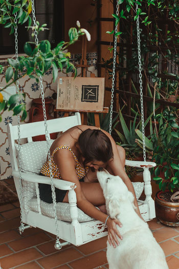 Woman with dog sitting on potted plant