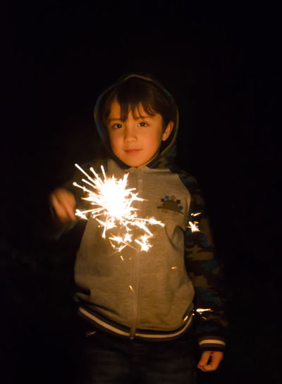 Portrait of cute boy holding sparkler at night