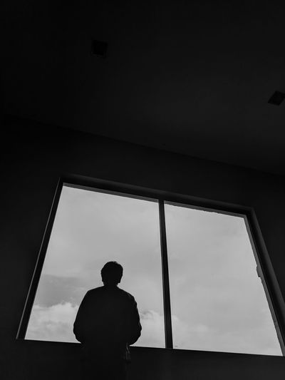 Rear view of man looking through window while standing in room