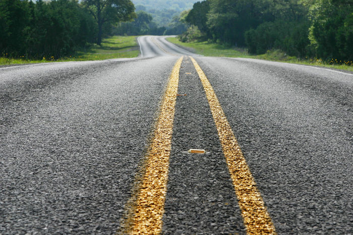 Low angle view of a road in the Texas hill country Asphalt Highway Hill Hill Country Hill Country Texas Low Angle View No People Road Springtime Stripes Straight Lines Sunlight Texas Trees USA