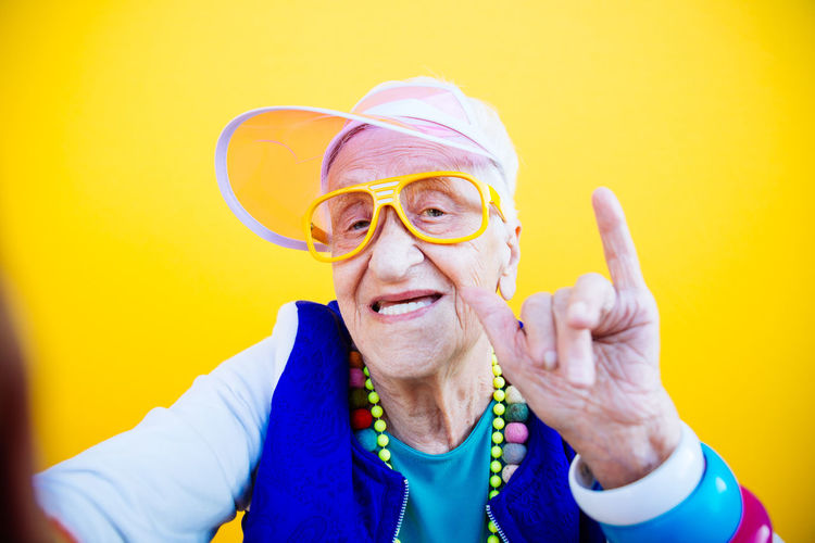 Portrait of happy senior woman gesturing against yellow background